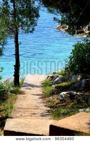 Road Leading To A Beach With Clear Water And Blue Slippers