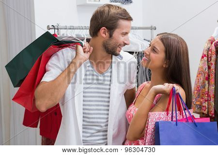 Smiling couple with shopping bags looking at each other at a boutique
