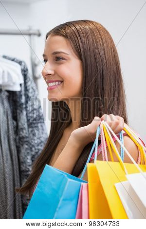 Smiling woman with shopping bags at a boutique