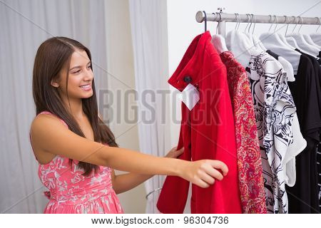 Smiling woman looking at red coat at a boutique
