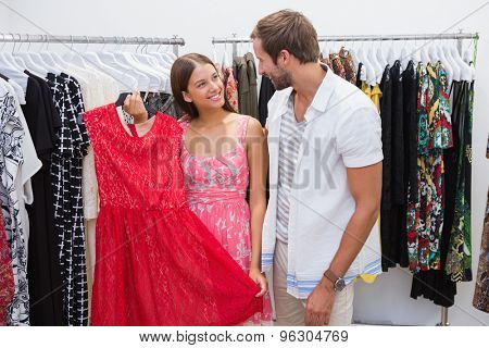 Happy couple choosing new clothes at the clothing shop