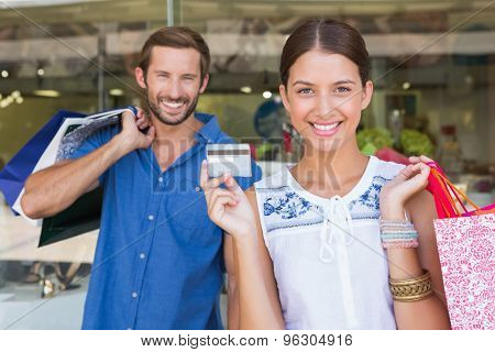 Young happy couple looking at camera after shopping