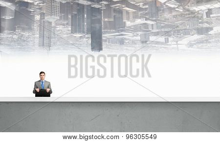 Young smiling businessman sitting with briefcase in hands
