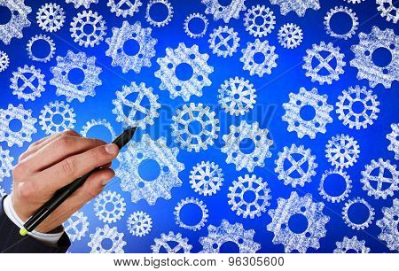Close up of hand drawing gears mechanism with marker