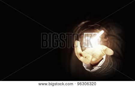 Close up of businessman's hand holding check mark icon in palm