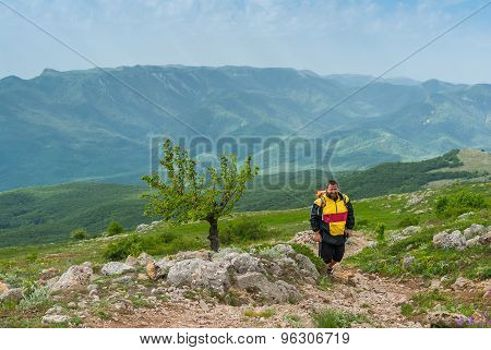 Hiker walks through Chatyr-Dah mountainous massif in Crimean mountains
