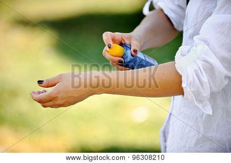 Woman's Hands Using Sunscreen