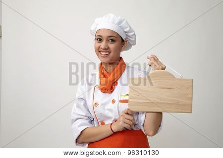 Indian woman with chef uniform holding a woden plank
