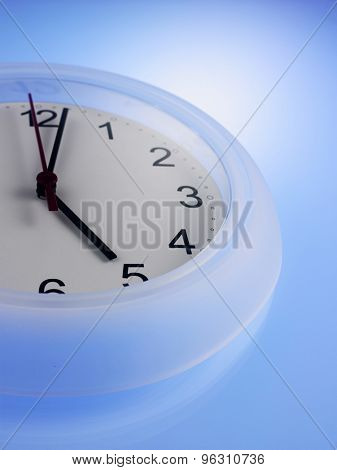 Close up of Clock showing 5 o'clock on a blue wall