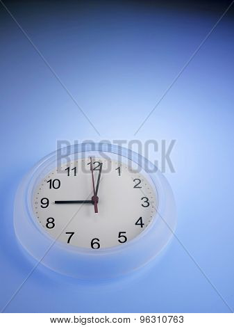 Clock showing 9 o'clock on a blue wall