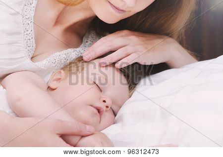 Cute Little Sleeping Baby Girl With Her Caring Mother