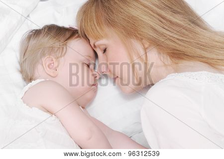 Portrait Of Little Sleeping Baby Girl With Her Caring Mother