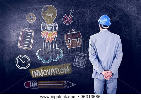 Businessman with helmet turning his back to camera against black background