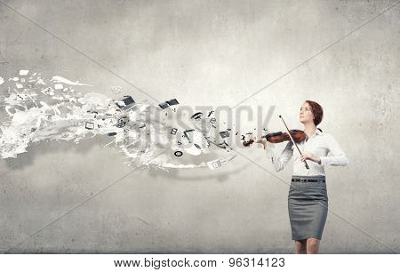 Young pretty businesswoman on cement background playing violin