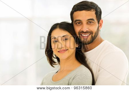 romantic young indian couple hugging indoors