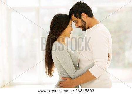 affectionate young couple hugging at home