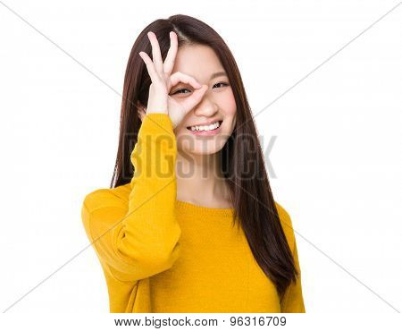 Woman with ok sign on eye