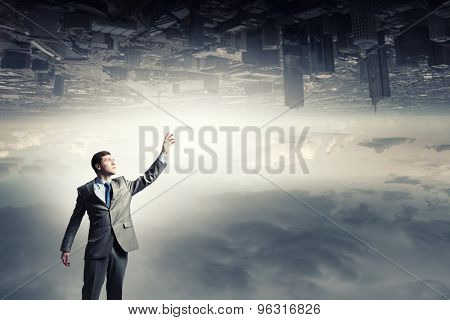 Young businessman reaching hand above to touch city reflection