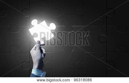 Close up of businessman hand holding glowing jigsaw element