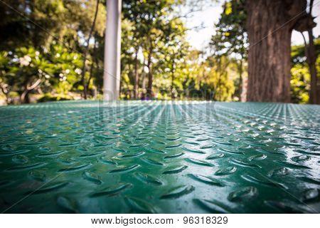 Green Metal Floor With Blur Of The Garden