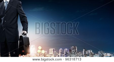 Rear view of businessman and night city at background