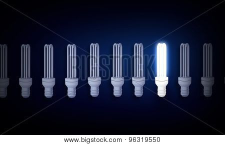 Light bulbs on dark background with one burning