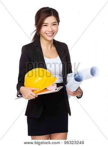 Young engineer with helmet and blue print