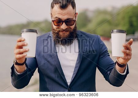 bearded man carrying coffee