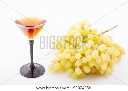a large bunch of grapes with a glass of wine on a white background