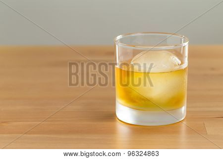 Whiskey drink on wood with ice cube