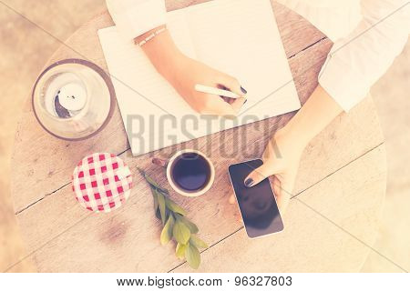 Young Girl Writes In A Notebook With Cell Phone And Cup Of Coffee, Top View