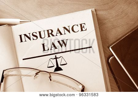 Paper with words Insurance Law and glasses.