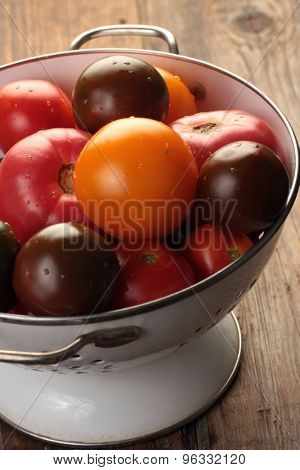 Tomatoes in a colander on a rustic table