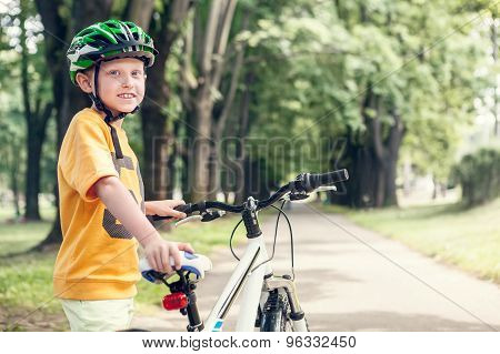 Smiling Boy With New Bicycle In Park