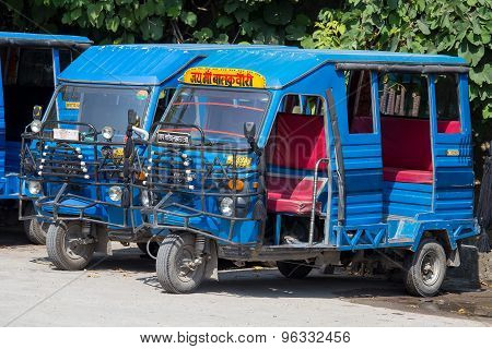 Auto rickshaw taxis on a road.