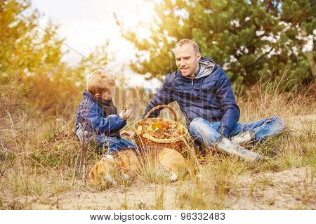 Father And Son With Full Basket Of Mushrooms Rest In Forest