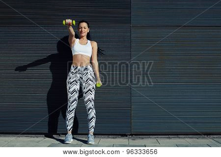 Female working on her arms training bicep curls with copy space background for your text message