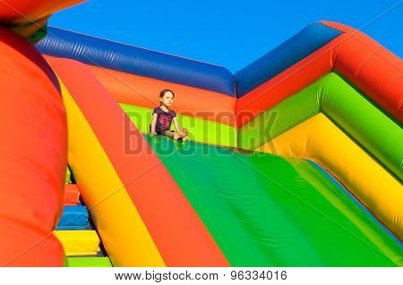 Little girl sitting on inflatable trampoline. The child is riding high in a slide.