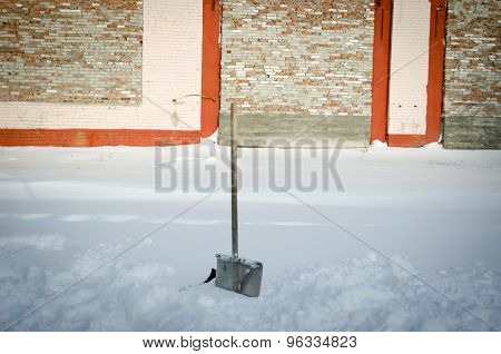 Shovel In Snowdrift On A Background Of A Brick Wall