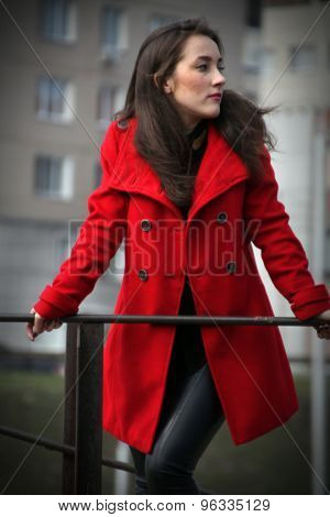 Beautiful Girl In A Red Coat Holding On To The Railing