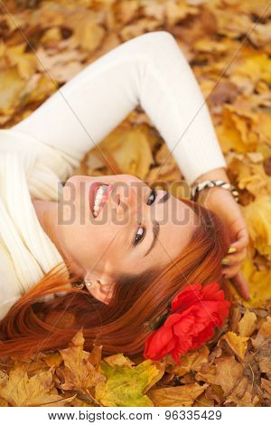 Young Woman Lying Among Red Leaves