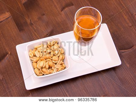 Cocktail and salted nuts on wood from above