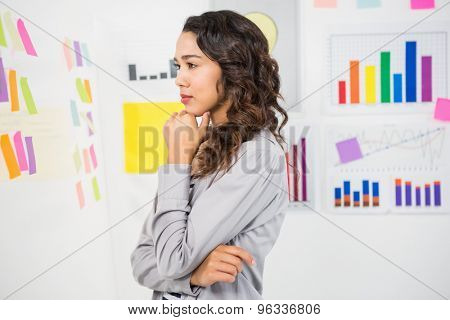 Young thinking businesswoman looking at sticky notes in the office