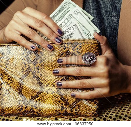 pretty fingers of african american woman holding money close up with purse, luxury jewellery on pyth