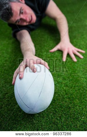 Determined rugby player scoring a try on the grass