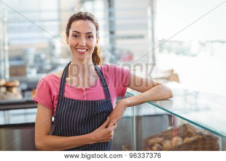Pretty waitress leaning on counter at the bakery