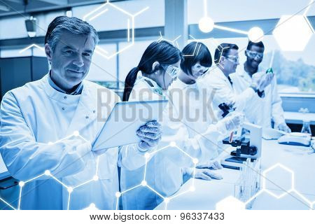 Science graphic against smiling chemist using tablet pc