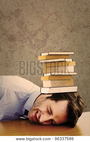 Casual businessman sleeping at his desk against grey room