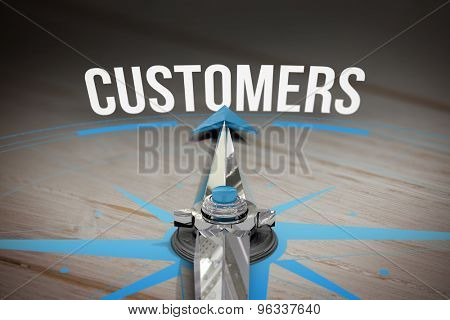 The word customers and compass against brown wooden background