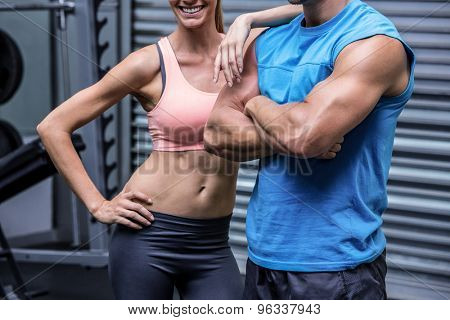 Young woman smiling with a young man in the crossfit gym
